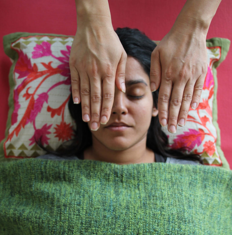hands in reiki position above woman