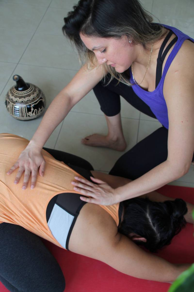 teacher helping student in yoga pose